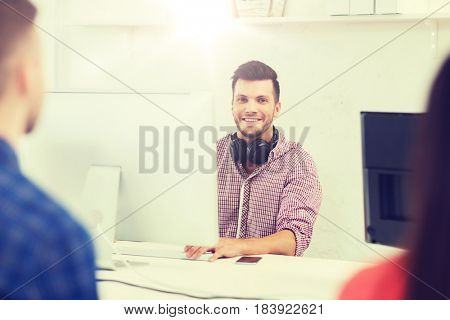 business, startup, education and people concept - happy young creative man with computer and headphones working at office