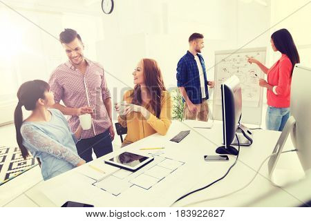 business, communication, startup and people concept - happy creative architect team or students with blueprint drinking coffee at office