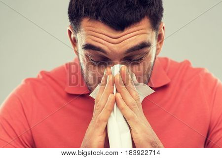 health care, flu, allergy, hygiene and people concept -sick man blowing nose to paper napkin at home