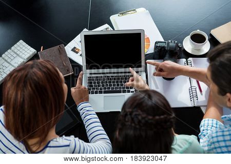Graphic designers discussing over laptop in creative office