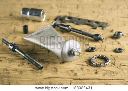 Tools and grease for bike repair on the wooden table. The concept of Bicycle repair.