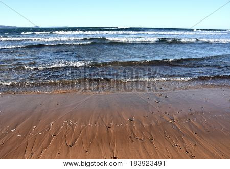 Tropical beach in the sun beach background scene with clear blue sky and waves rolling on the beach. White foam on beach water nature. Summertime blue sea and waves yellow sun and sand.