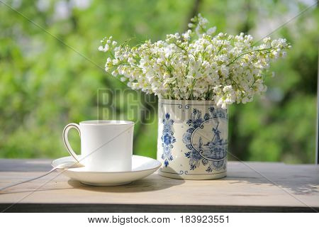 Still life with a white porcelain cup and vase from Delft porcelain with white flowers in the morning light