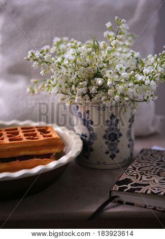 Still life with liège delicious waffles, notepad and white flowers in the Dutch porcelain vase