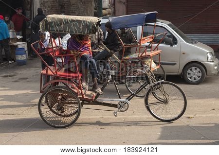 DELHI INDIA-DEC 20 : rickshaw driver waiting for passengers near old delhi railway station in old delhi on december 20 2014 india. there are many rickshaw taxi in area of delhi
