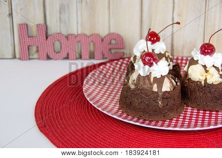 ice cream sundae in brownie cup with whipped cream and maraschino cherry on gingham plate