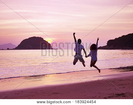 young asian couple cheering and rejoicing on beach as the sun rising.