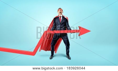 A businessman in a red flowing cape trying to lift a large red arrow upwards on blue background. Investment and banks. Business profit. Stock index.