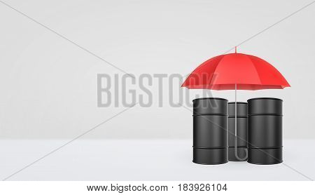 An open classic red umbrella with a handle vertically placed over black oil barrels. Protection and safety. Oil and gas industry. Business insurance.