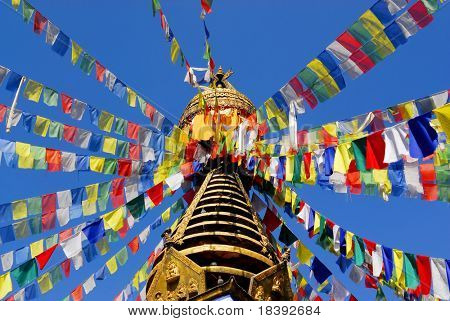 nepalese stupa with colorful prayer flags and clear blue sky