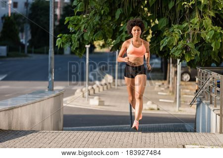 Runner athlete running on city street. Fitness workout concept.