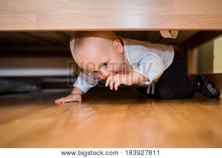 Adorable baby boy hiding under the bed
