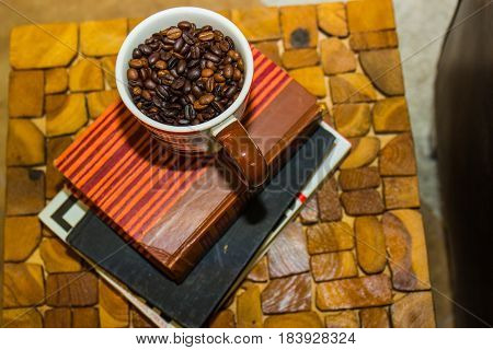Cup Of Coffee Beans Sitting On Stack Of Books