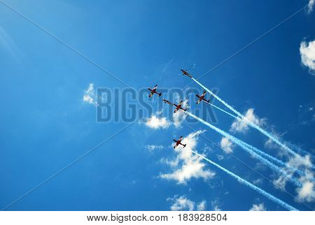 MELBOURNE, AUSTRALIA - MARCH 20, 2016: Air show at Formula 1 Australian Grand Prix. Red jets flying across bright blue skies, leaving trails