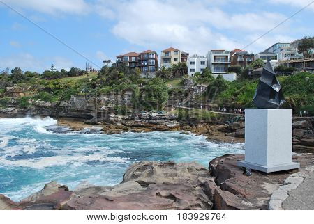 SYDNEY, AUSTRALIA - NOVEMBER 03, 2014: A monument from Sculpture by the Sea project along with household property on the Bondi to Bronte coastal walk. Sculpture by the Sea is one of the world's largest free to the public sculpture exhibitions.