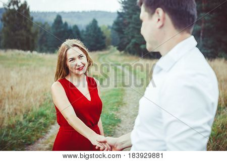 A nice couple in blue jeans and white t-shirts looking at each other happily standing back to