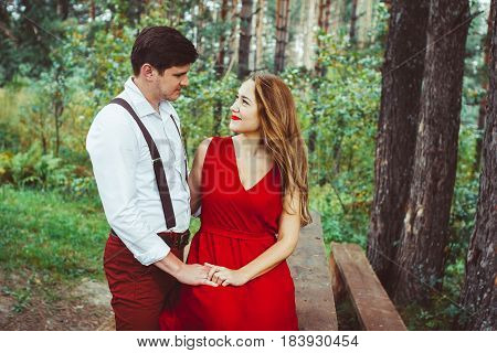 Smiling lovely couple sitting on bench in forest and looking away