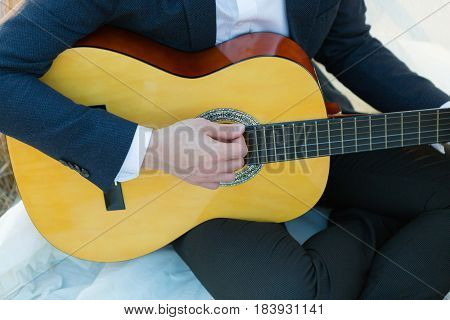 Man's hands playing music at wooden acoustic guitar