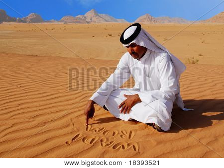 Traditional arabic man writing in the sand in Wadi Rum desert, Jordan