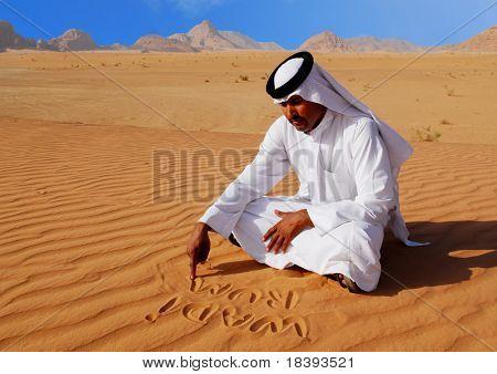 Traditionelle arabische Mann schreiben im Sand in Wadi rum Wüste, Jordanien