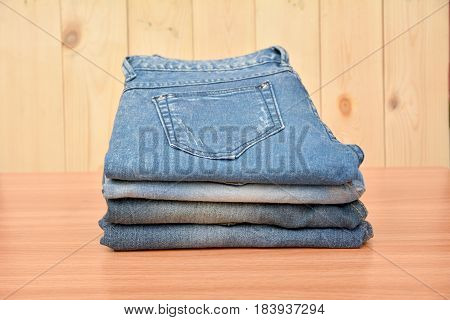 Blue jeans folded stack on wooden table and on wooden background.