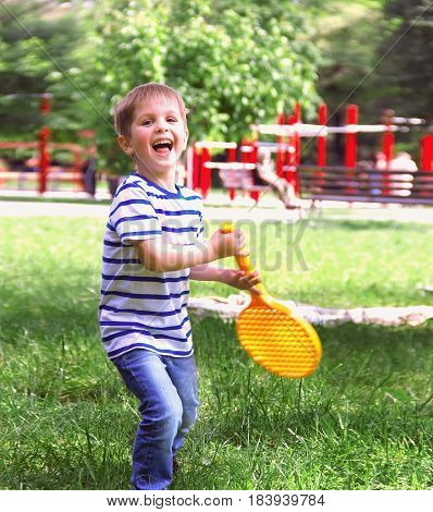 Little boy playing tennis Happy cheerful boy holding a racket standing on the green grass a champion a happy childhood soft focus