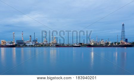 Industrail petroleum refinery river front at twilight