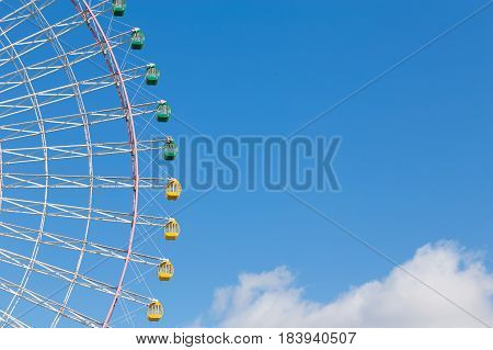 Path of funfair giants wheel against blue sky background