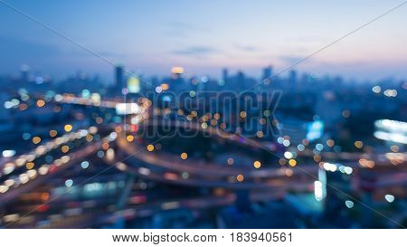 Top view blurred bokeh light city downtown and highway interchanged abstract background
