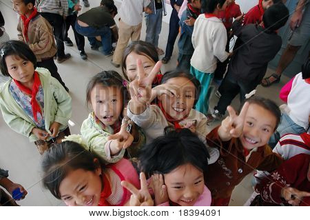 DALI, CHINA, OCTOBER 2005; Happy school kids greet tourists as they prepare for going back to school for the first semester of the year in Dali, China.