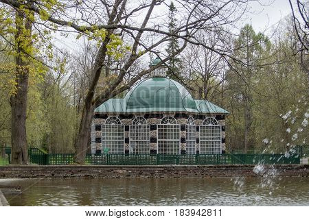 PETERHOF RUSSIA - MAY 10 2015: Decorative pavilion with green roof near the pond and fountain at Peterhof park near St. Petersburg Russia.