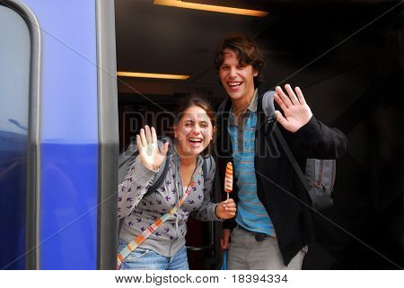 Young couple in their twenties laughing and waving goodbye from departing train in holland