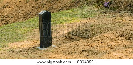 Newly dug grave mound with granite marker in wooded area on mountain in South Korea