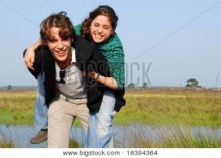 Playful young couple in their twenties playing piggyback with background of heath and lake