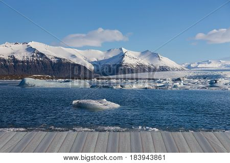 Opening wooden floor Blue lagoon winter season with snow covered mountain background Iceland natural landscape