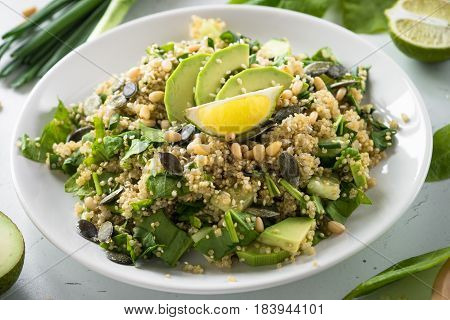 Fresh quinoa salad with spinach avocado greens seeds and Pine nuts. Clean eating detox and vegetarian food.
