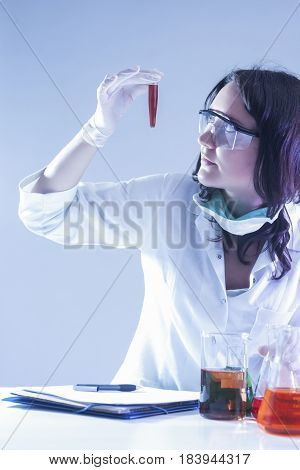 Medicine Ideas and Concepts. Female Laboratory Worker Looking at Flask Filled With Liquid Chemical During Experiment.Vertical Image