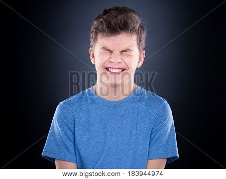 Half-length emotional portrait of caucasian teen boy with blinking or closed eyes. Funny teenager wearing blue t-shirt on black background.
