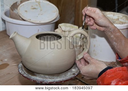 Ceramic artist working with a tea pot