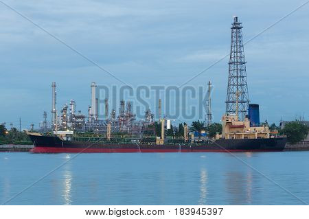 Oil refinery river side with boat tank at twilight