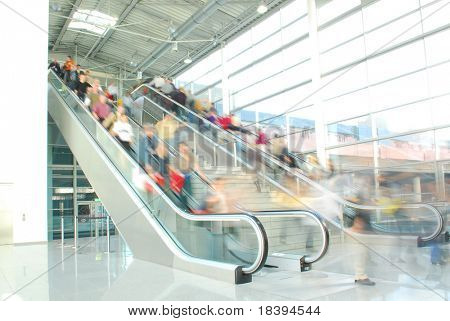 People rushing to work on escalators in business center, mall or airport with motion blur