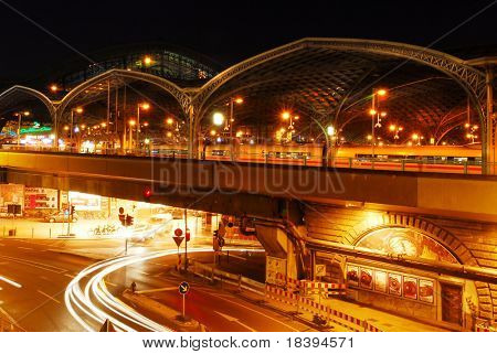 Beautiful lit railway station of Cologne at night with moving car lights in the tunnel underneath