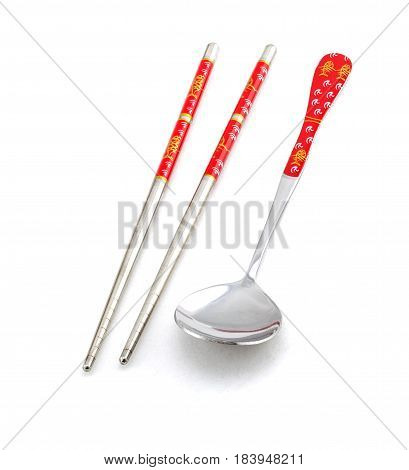 The chopsticks and tablespoon on white background
