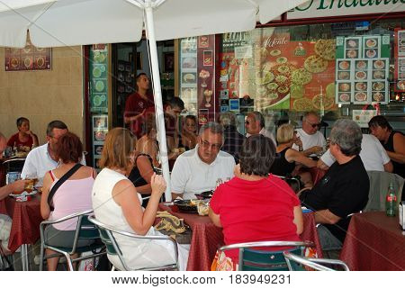 CADIZ, SPAIN - SPETMEBER 8, 2008 - Tourists relaxing at a pavement cafe along Colunela Cadiz Cadiz Province Andalusia Spain Western Europe, September 8, 2008.