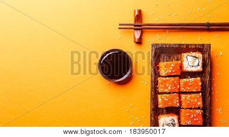 Rolls with chopsticks on isolated orange background