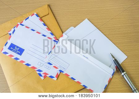 Air mail letter and pen on wood background.