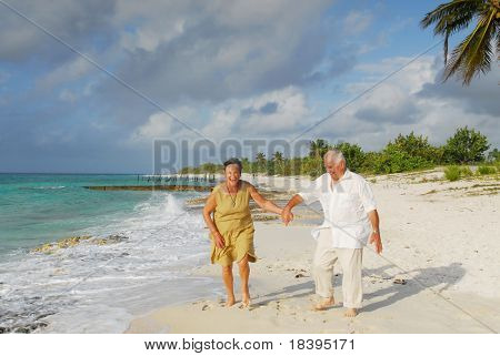 Active senior couple walking on the beach, getting wet, enjoying retirement on tropical destination: Maria la Gorda on caribbean island Cuba