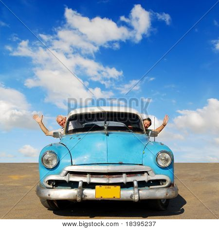 European senior couple having fun touring around Cuba, in an blue vintage oldtimer car