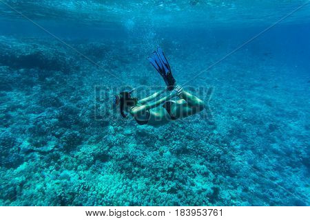 Underwater Image Of A Young Lady Snorkeling And Diving In A Tropical Sea With Hands On Legs. Beautif
