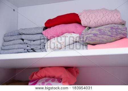 Winter clothes nicely arranged on a shelf. Tidy wardrobe with colorful clothes and accessories.